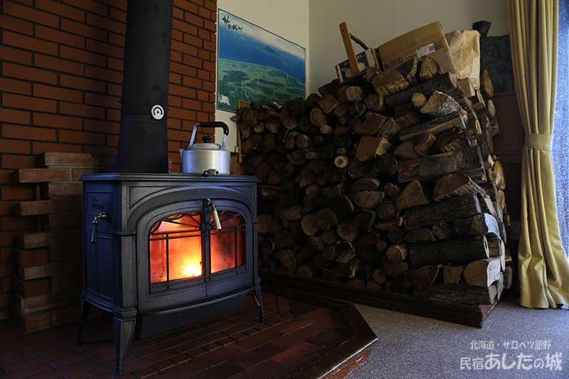 部屋に積まれた薪とストーブ